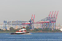 "Tugboat ""Captain D"" in Newark Bay, with the container cranes of the New York Container Terminal, the Goethals Bridges, and the Arthur Kill Vertical Lift Railroad Bridge in the background."
