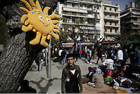 Pictured: A soft toy depicting a smiley sun hands from a tree in Victoria Square, Athens Monday 29 February 2016<br /> Re: Hundreds of migrants have been living in Victoria Square in central Athens Greece