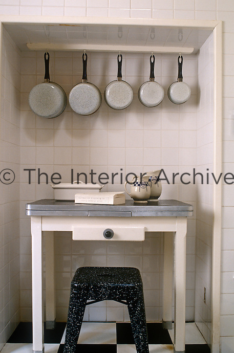 In the kitchen a collection of enamel saucepans hangs in an alcove which houses a retro zinc-topped table and Bakelite kitchen stool