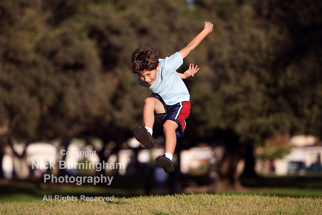Happy young boy jumping and playing in the park - copy space left and right