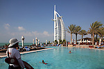 A safeguard watching the swimming pool of Jumeirah Beach Hotel with the Burj al Arab hotel in the background. Dubai. Unite Arab Emirates