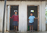 Kabita Chepang, 10, and Bipana Chepang, 7, emerge from the latrines at the Shri Pashupati Praja Primary School in the village of Tanglichowk, in the Gorkha District of Nepal. In the aftermath of the April 2015 earthquake that ravaged Nepal, the ACT Alliance helped people in this village with a variety of services, including latrines, emergency shelter, livelihood projects and school construction. School latrines are an important component of keeping girls in school past puberty.<br /> <br /> Parental consent obtained.