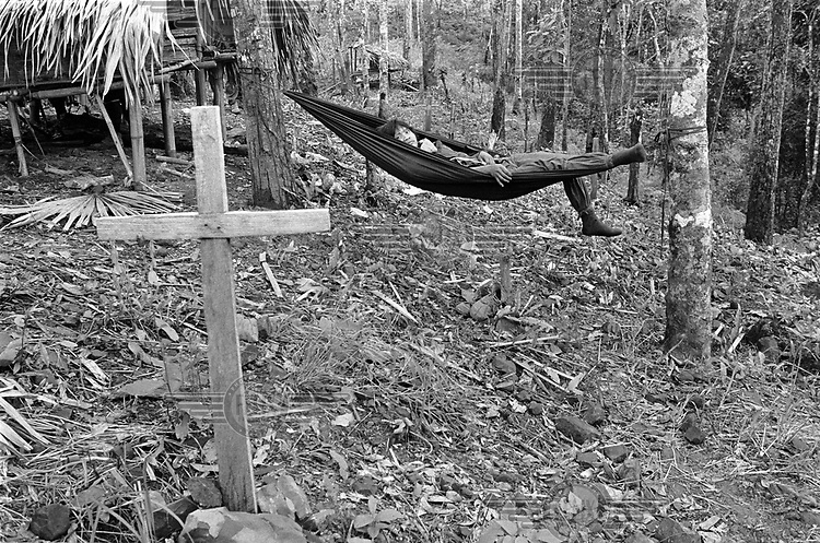 A Karenni guerrilla fighter relaxes on a hammock in a cemetery.