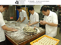Chefs prepare dim sum dumplings at Victoria seafood in Hong Kong.