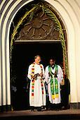Zanzibar, Tanzania. A black priest and a white priest at the door of their church.
