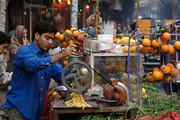 A vendor makes fresh orange juice at an outdoor fruit juice stall in the Old City of Lahore, where there are numerous places to eat and drink on the street.