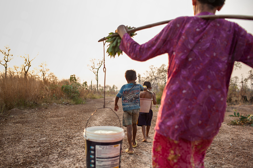 After being relocated from her village to make way for a sugar cane plantation, Savy collects water with her two grand-children. With no work opportunities in the relocation village Svay's daughter left to work in Thailand, she has not had news since her departure six months ago. Savy cares for her daughter's two sons. O'bat Moun relocation village. 12 Feb. 2013. © Nicolas Axelrod / Ruom