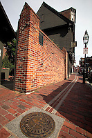 Round bronze marker emblem on the red brick Freedom Trail in North Boston with Paul Revere House Boston MA in back<br />