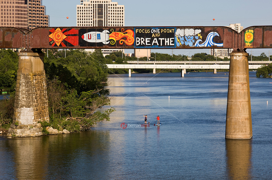 "SUP stand up paddle board couple row under the ""Focus One Point And Breathe"" colorful graffiti painting with a USA space rocket on a the railroad bridge over Lady Bird Lake, overlooking the Austin skyline."