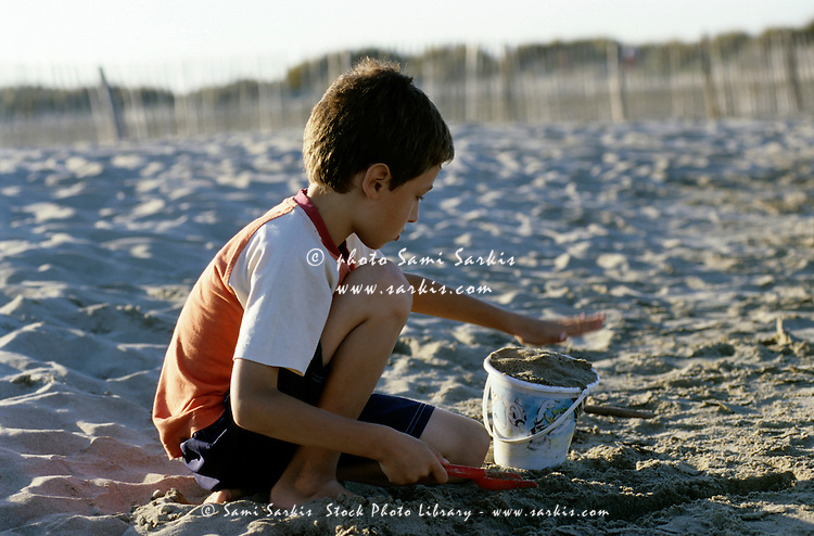 Young boy building a sandcastle on a sandy beach at sunset, Camargue, France.