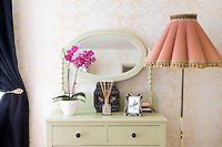 In the master bedroom a vintage chest of drawers is painted the palest of pistachio greens to contrast with oyster-pink floral wallpaper, the salmon-pink shade of an adjacent standard lamp and a shocking pink orchid on top