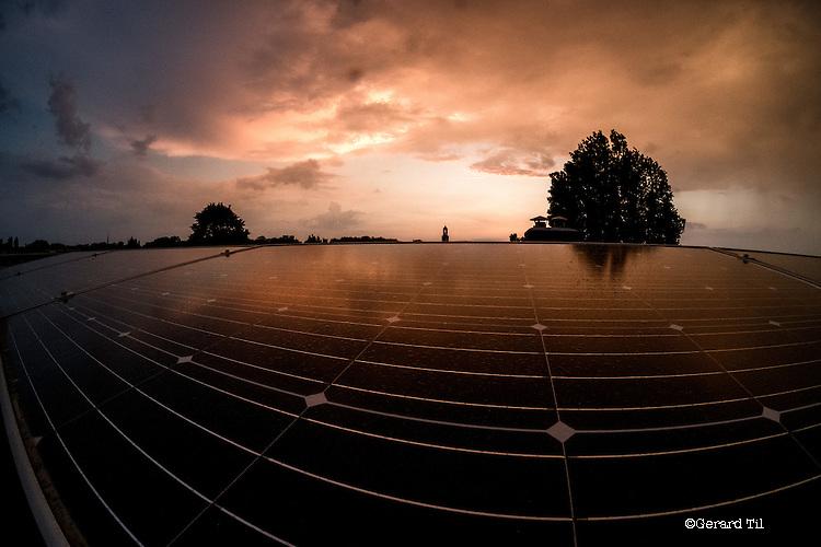 Nederland,Utrecht,   04-05-2016 Zonnepanelen in het avondlicht op het dak van een rijtjeshuis uit 1930 in de Utrechtse wijk Oudwijk. Op de achtergrond de Domtoren .FOTO: Gerard Til / Hollandse Hoogte