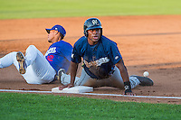Malik Collymore (34) of the Helena Brewers slides safely into third base as Jimy Perez (12) of the Ogden Raptors tries to handle the throw in Pioneer League action at Lindquist Field on August 17, 2015 in Ogden, Utah. Ogden defeated Helena 7-2.  (Stephen Smith/Four Seam Images)
