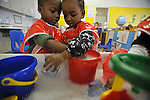 Jeremiah Taylor, 3, and Daisha White, 4, play together beside a tub of water and toys in Room 113 at the Educare Early Childhood Center in Chicago on November 21, 2008.  The pre-K daycare center is a model for head start, funded privately by the Gates and other foundations, that cares for and educates infants, toddlers, and 3- and 4-year old pre-school children.