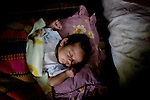 A baby, born from a mother addicted to drugs, sleeps peacefully. ..Korsang Khmer is an outreach and preventative care program for HIV/AIDS and needle exchange for drug users in the slums of Phnom Penh.