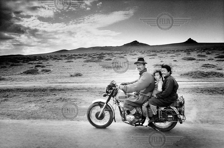 Family travelling to the capital Ulaan Bator by motorbike.