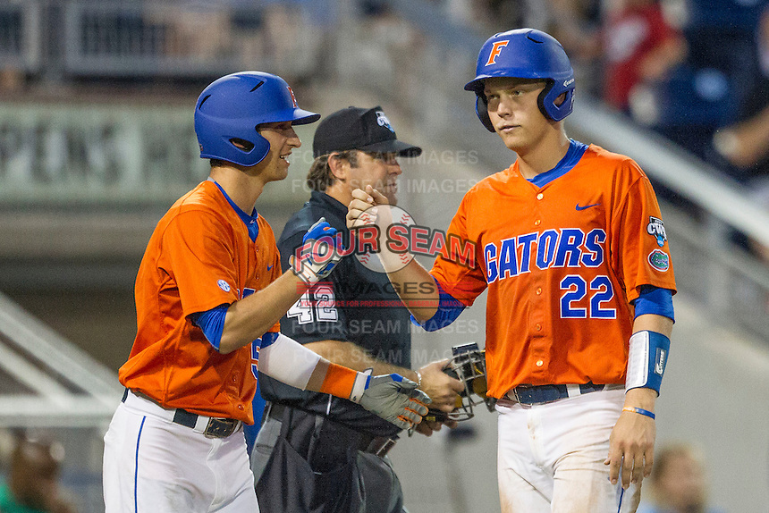 Florida Gators catcher JJ Schwarz (22) is greeted by teammate Dalton Guthrie (5) after scoring against the Virginia Cavaliers in Game 13 of the NCAA College World Series on June 20, 2015 at TD Ameritrade Park in Omaha, Nebraska. The Cavaliers beat the Gators 5-4. (Andrew Woolley/Four Seam Images)