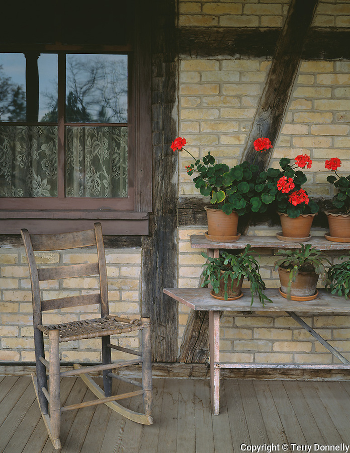 """Old World Wisconsin State Historic Site, Waukesha County, WI<br /> Geraniums and rocker on Koepsell House porch with a """"fachwerk"""" style wall -(circa 1850)"""