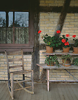 Old World Wisconsin State Historic Site, Waukesha County, WI<br /> Geraniums and rocker on Koepsell House porch with a &quot;fachwerk&quot; style wall -(circa 1850)