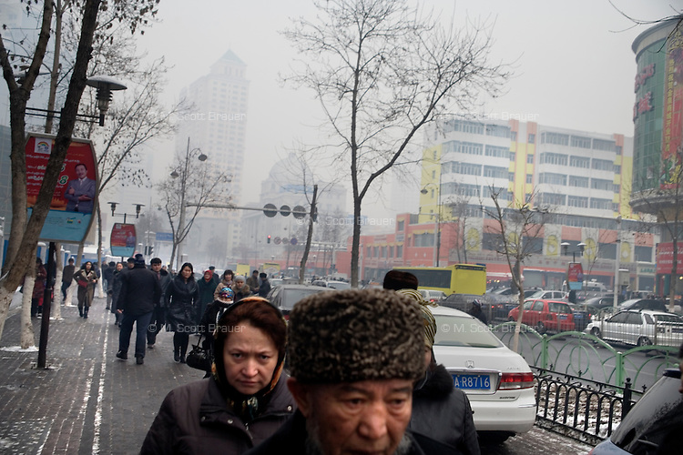 Uighurs walk past new construction in the Uighur section of Urumqi, Xinjiang, China. The city is divided between Han and Uighur ethnic groups and in 2009 saw violent clashes between the groups.
