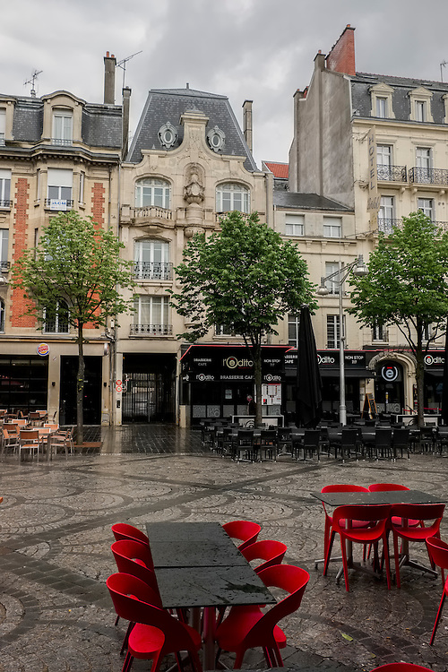 A vacant outdoor eating area in the central area of Reims awaits the beginning of a new day.