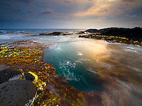 At sunset, waves rush over and into large holes in the algae-covered rocky shelf of Keahole Point, Big Island.