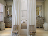 In this bedroom at Blakes Hotel in London exqusite mother-of-pearl inlaid chests-of-drawers flank a muslin-draped four-poster bed