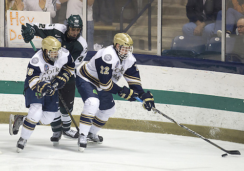 December 07, 2012:  Notre Dame left wing Mario Lucia (#22) skates with the puck with Notre Dame center T.J. Tynan (#18) as Michigan State defenseman Jake Chelios (#42) defends during NCAA Hockey game action between the Notre Dame Fighting Irish and the Michigan State Spartans at Compton Family Ice Arena in South Bend, Indiana.  Notre Dame defeated Michigan State 3-2.
