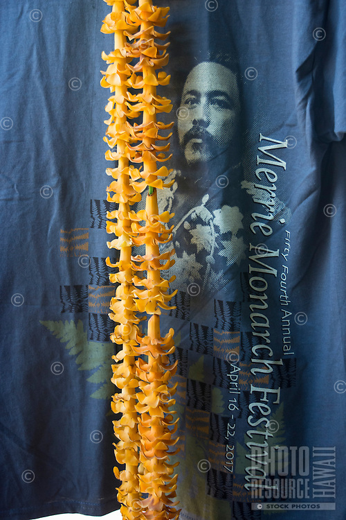 An orange puakenikeni lei on display with a Merrie Monarch Festival t-shirt featuring King David Kalakaua, Hilo Farmers Market, Big Island of Hawai'i. The historic festival is like the Olympics of hula and takes place every April in Hilo.