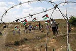 Protesters hold Palestinian flags during a protest marking Land Day near the border between Israel and the Gaza Strip March 30, 2010. March 30th marks Land Day, the annual commemoration of protests in 1976 against Israel's appropriation of Arab-owned land in the Galilee. Photo by Ashraf Amra