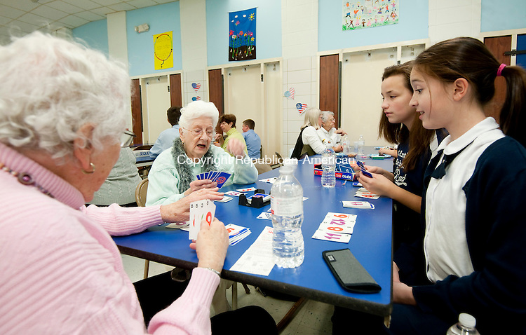 WINSTED, CT--- -112215JS05--Winsted residents and church parishioners Leona Mangione, left, and Madeline Brady, second from left, plays a card game of Skip-Bo with St. Anthony School seventh grade students Aubrey Landi and Madison Fritch, right, during a visit to the Winsted school on Monday. The school hosts these gatherings to foster  intergenerational friendships and learning. <br /> Jim Shannon Republican-American