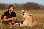 Botswana, Kalahari, Valentin Gruener with a lioness; he raised her on a private reserve from a small dying cub to a healthy adult