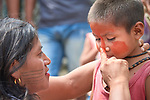 A woman paints a child's face with urucum before a march by indigenous people through the streets of Atalaia do Norte in Brazil's Amazon region on March 27, 2019. They were protesting a central government plan to turn control of health care over to municipalities, in effect destroying a federal program of indigenous health care. Indian rights activists are worried that the government of President Jair Bolsonaro is reducing or eliminating protections for the country's indigenous people.