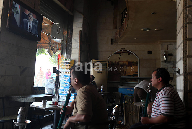 Egyptians watch television in a cafe at Cairo's Tahrir square, Egypt, 14 June 2012. Media reports on 14 June state that the Supreme Constitutional Court ruled that Ahmed Shafik could stand in the presidential election run-off, saying a law banning officials who served under Hosni Mubarak from running for office was unconstitutionali. Photo by Majdi Fathi