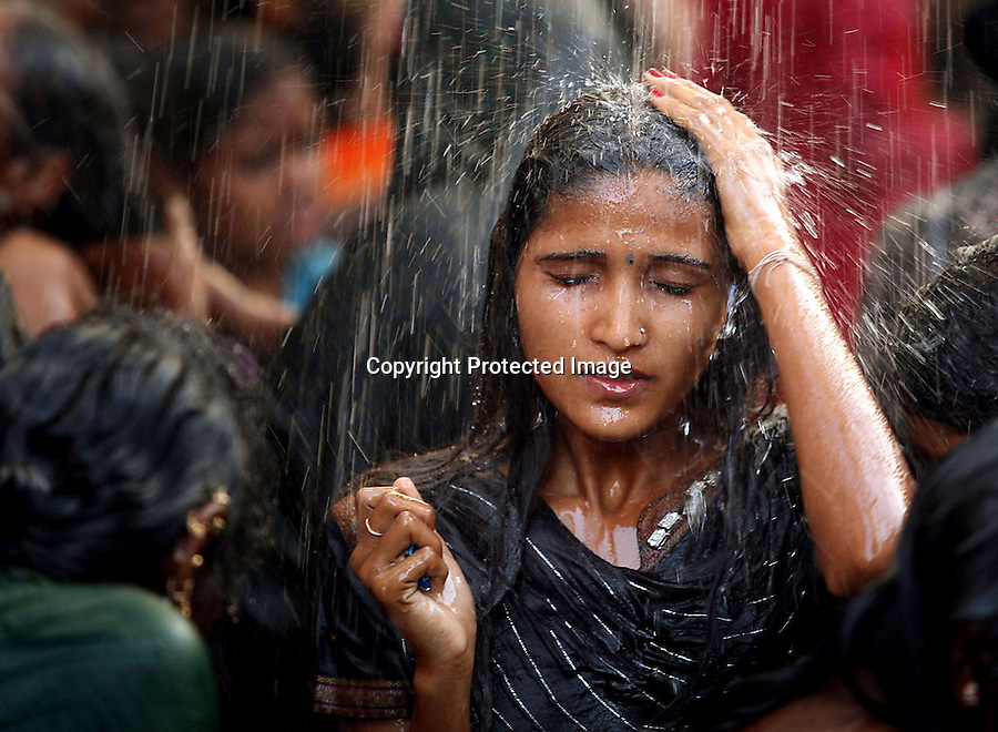 A young woman bathes in a communal bathing area before worshipping at the Yellamma temple during the Yellamma Jatre (festival) in Saundatti, India. As part of Yellamma custom, all worshippers must wash before worshipping and during the full moon festival.