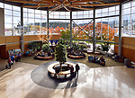 People in a waiting lounge of Victoria International Airport YYJ, lobby interior with beautiful colorful autumn trees outside. Victoria, British Columbia, Canada 2017.