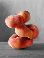 Donut Peaches piled on top of each other against a black background