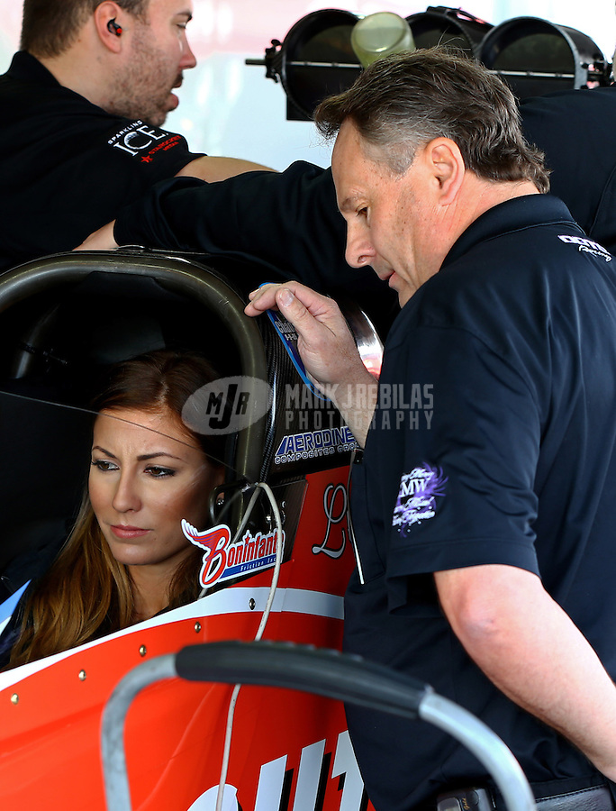 Feb 8, 2015; Pomona, CA, USA; Crew chief Doug Cook watches NHRA top fuel driver Leah Pritchett warm up the car in the pits during the Winternationals at Auto Club Raceway at Pomona. Mandatory Credit: Mark J. Rebilas-