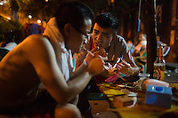 "Neighborhood locals eat at a nameless shaokao barbecue restaurant on the sidewalk near the west gate of the Ciqikou area of Shapingba district in Chongqing, China. The pair, who said they live nearby, said they were eating mostly chicken meat and chicken skin. ""This is the best shaokao,"" they said, explaining why there were eating at the restaurant this evening, ""The flavor is the best."" Ciqikou's ancient town is a major tourist destination in Chongqing, but at night, the tourists disappear and locals come out to eat from street food vendors in the area.<br /> <br /> The restaurant is run by Liu Pang Wa, whose wife and two children also help. Most of the customers there are neighborhood locals, and the restaurant stays open until 3 or 4 am. Liu Pang Wa said his specialties are eggplant, pig brain, and fish. The area is close to western banks of the Jialing River in northwestern Chongqing city."