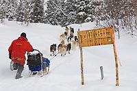 Ramey Smyths team leaves Finger Lake Chkpt past Iditarod Trail Sign Finger Lake Alaska 2006 Iditarod