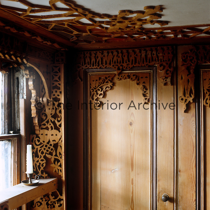 Detail of fretwork surrounding the window, top of the cupboard and on the ceiling
