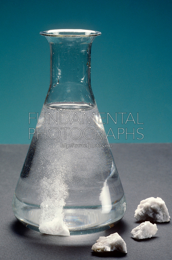 CALCITE MINERAL REACTS TO HYDROCHLORIC ACID<br /> An Exothermic Reaction<br /> Calcite placed in a flask of HCl reacts with the acid, forming calcium chloride and carbon dioxide, which appear in the solution as bubbles.