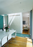 The contemporary dining room is separated from the living room by a sold partition and a section of glass floor