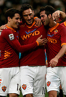 Calcio, Serie A: Roma vs Chievo Verona. Roma, stadio Olimpico, 8 gennaio 2012..Football, Italian serie A: Roma vs Chievo Verona. Rome, Olympic stadium, 8 january 2012..AS Roma forward Francesco Totti, center, is hugged by teammates Bojan Krkic, of Spain, left, and Miralem Pjanic, of Bosnia, after scoring for the second time on a penalty kick. AS Roma won 2-0..UPDATE IMAGES PRESS/Riccardo De Luca