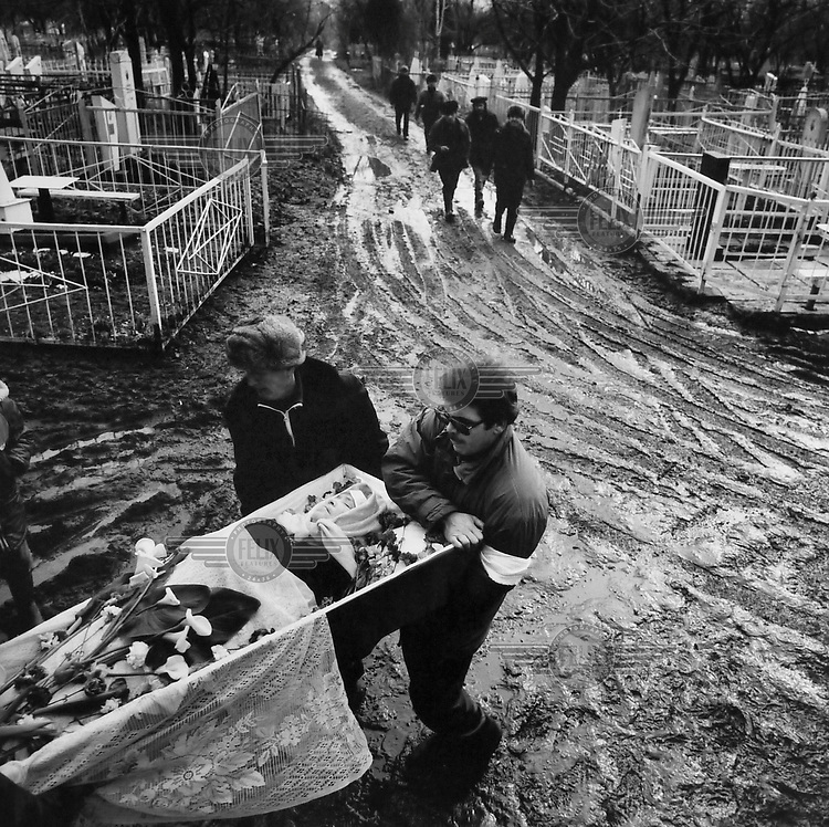 A burial at the local cemetery. Due to the harsh economic conditions after the collapse of the Soviet Union most people could not afford a relegious burial and had to make their own arrangements.
