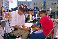 Asian American doctor checks the blood pressure of young boy at neighborhood health fair, San Francisco, California