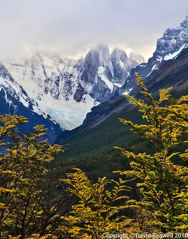 The elusive Cerro Torre shows it's base through the cloud cover of a summer storm over Parque Nacionales los Glaciares, Argentina.