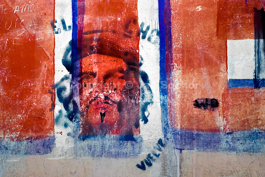 A spray paint stencil artwork, depicting the famous portrait of Che Guevara and saying 'El Che Vuelve' (El Che returns), is seen painted on the wall in the street of Vallegrande, Bolivia, 2 September 2002.