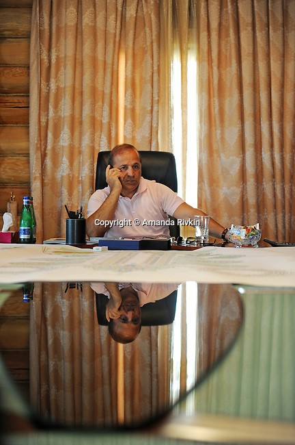 Ibrahim Ibrahimov, an Azerbaijani oligarch and billionaire, talks on his cell phone during a meeting at the on-site office of the Khazar Islands project near Sahil, Azerbaijan on July 18, 2012.  The brainchild of Ibrahimov, the artificial Khazar Islands project just southwest of the Azerbaijani capital Baku is being built at a projected cost of $100 billion with an anticipated 800,000 housing units.