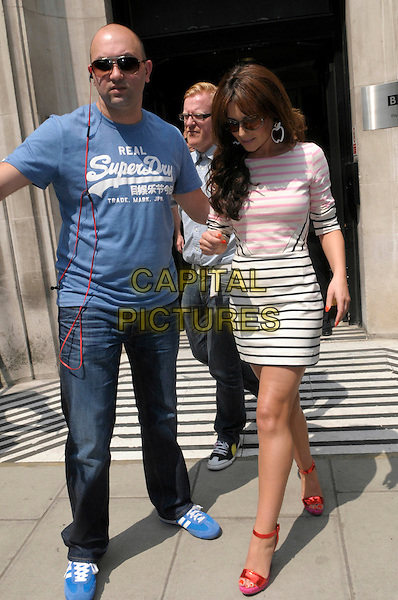 Cheryl Cole leaving BBC Radio 2, London, England..29th May 2012.full length white black pink striped stripes dress sunglasses shades minder bodyguard security blue t-shirt jeans denim looking down red sandals ankle strap shoes.CAP/IA.©Ian Allis/Capital Pictures.